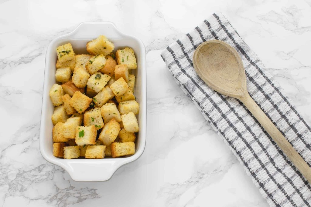 Freshly baked homemade croutons in a ceramic dish.