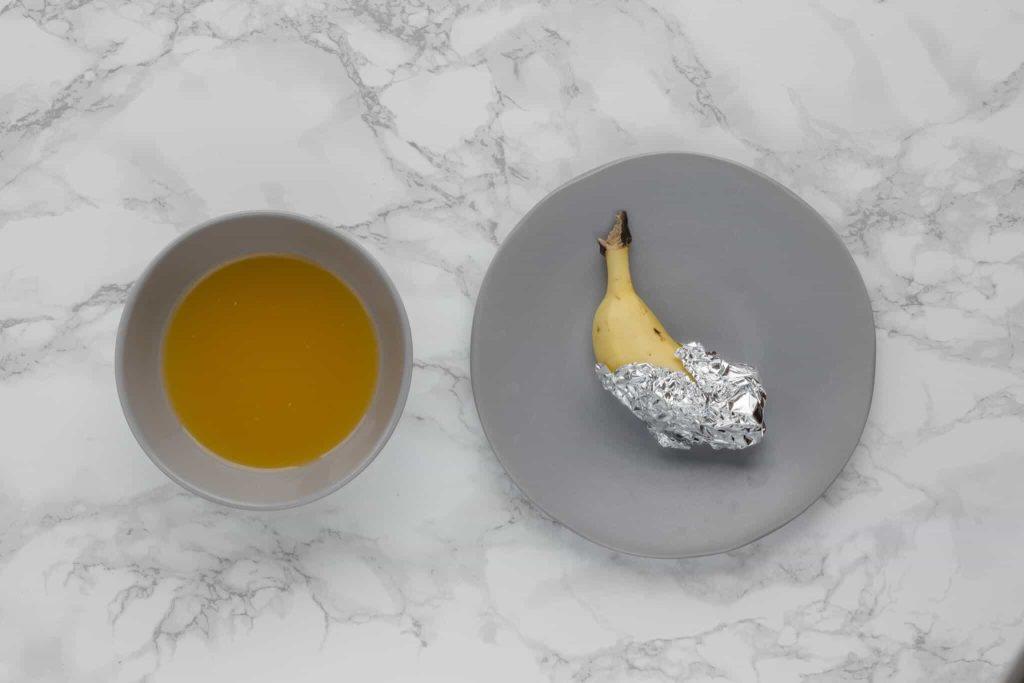 A cut banana wrapped in tin foil alongside a bowl or orange juice