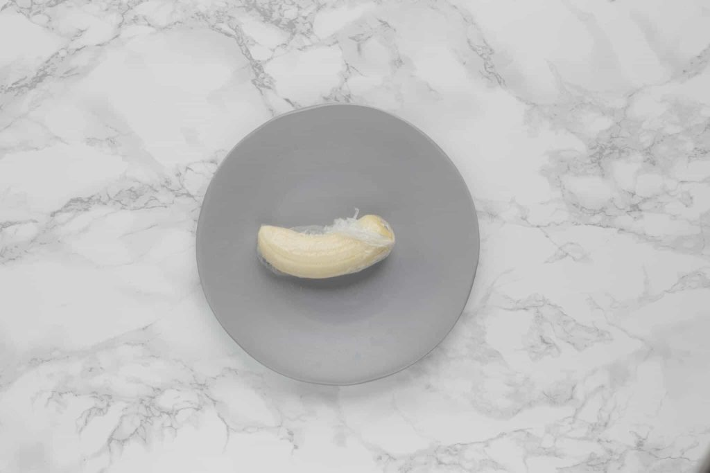 a peeled cut banana wrapped in plastic wrap