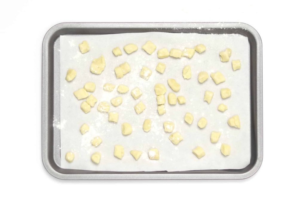 Gnocchi drizzed with flour on baking tray