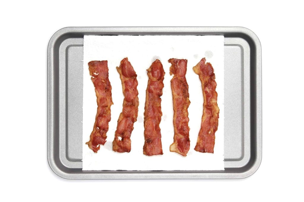 Bacon on a paper towel on a baking tray