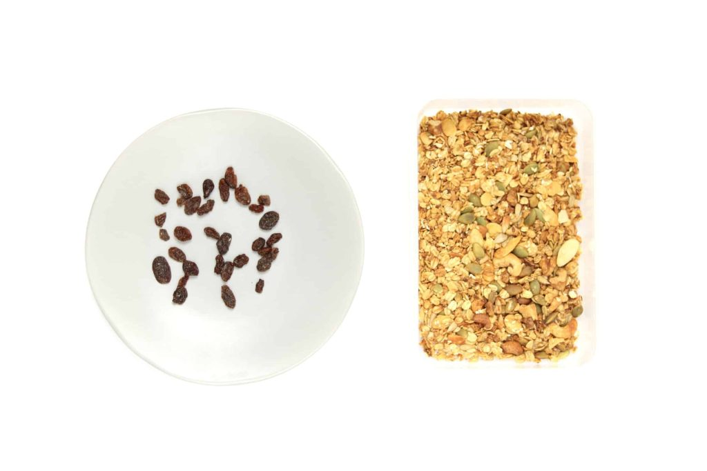 Granola and fruit separated on separate plates