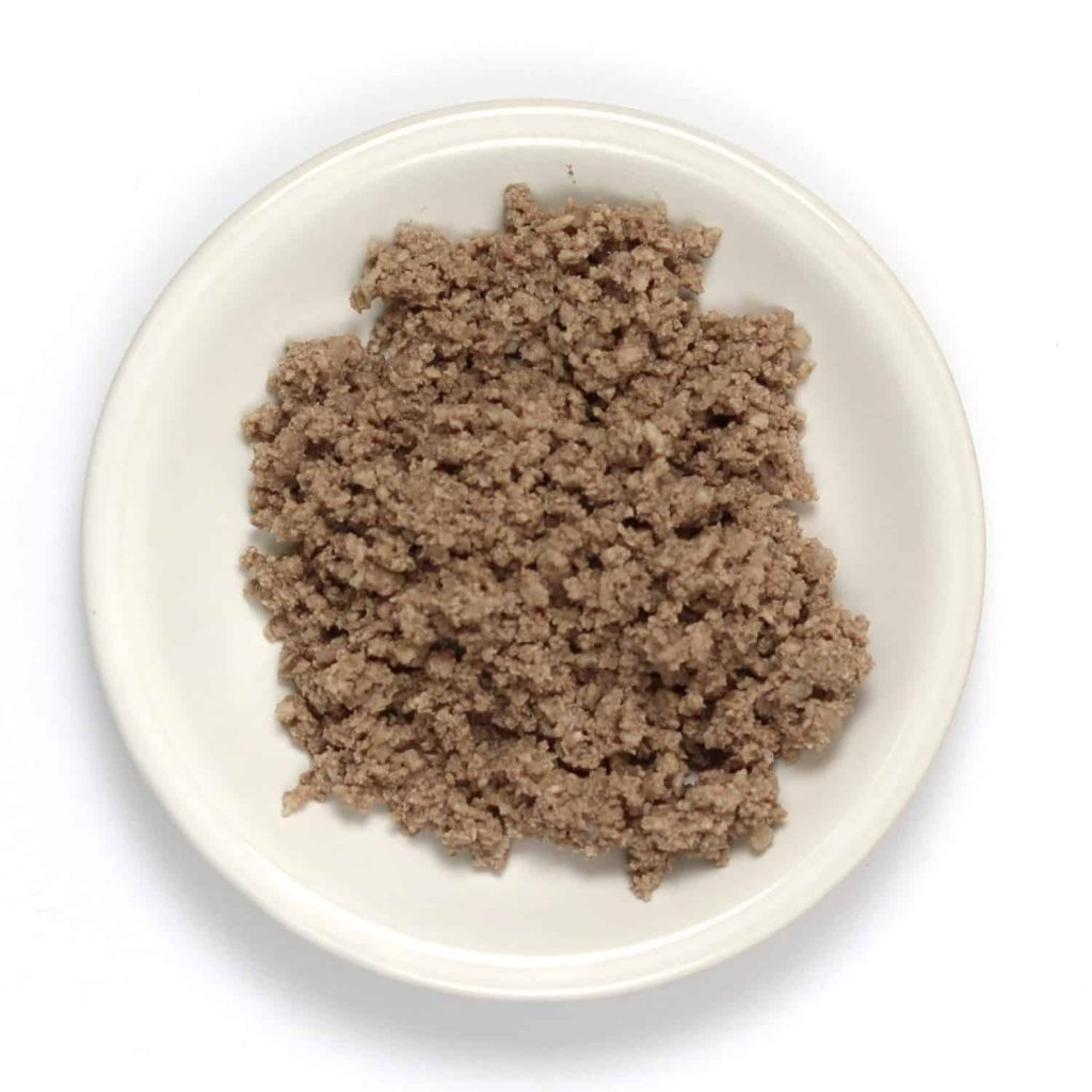 Finely crushed ground beef on a small plate after using a potato masher.