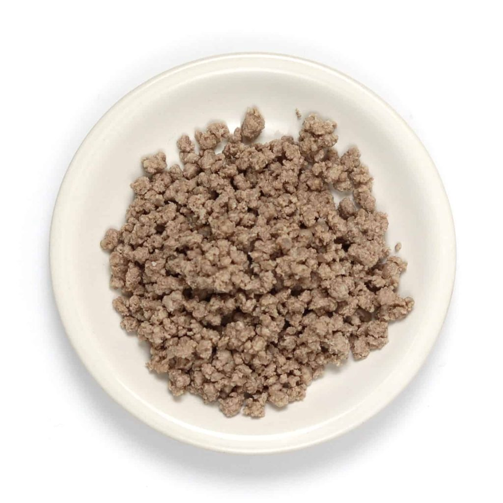 Ground beef on a small plate after being boiled and crushed.
