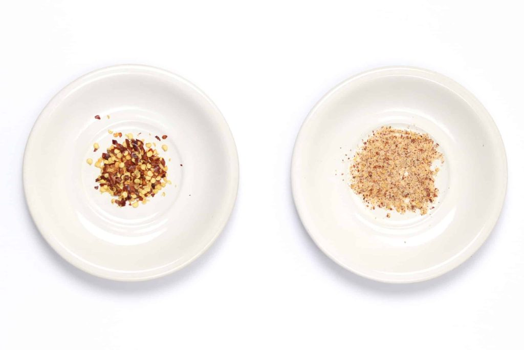 Side by side comparison of chilli flakes VS blended chilli popcorn seasoning with salt and chilli powder.