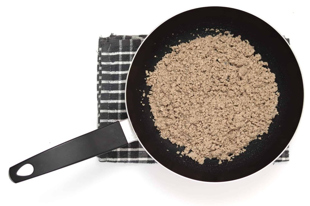 Frying pan filled with powdery ground beef after being cooked and mashed