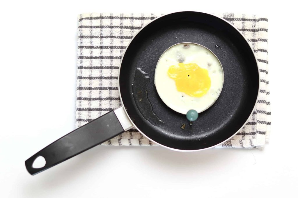 Egg being cooked in an egg ring in a frying pan