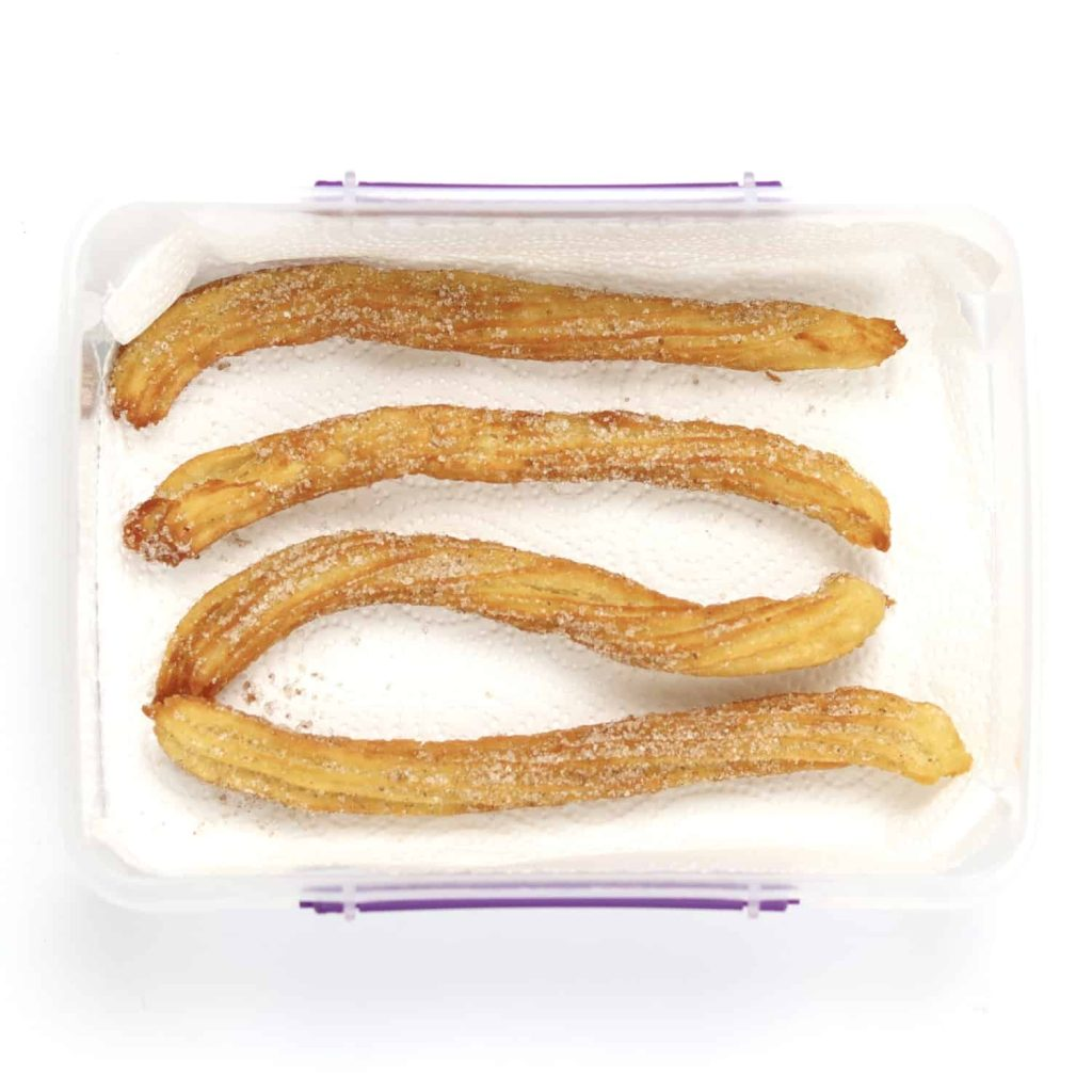 Churros placed inside an open container lined with kitchen roll