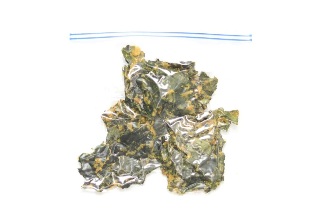 Kale chips stored in a freezer bag with the air removed