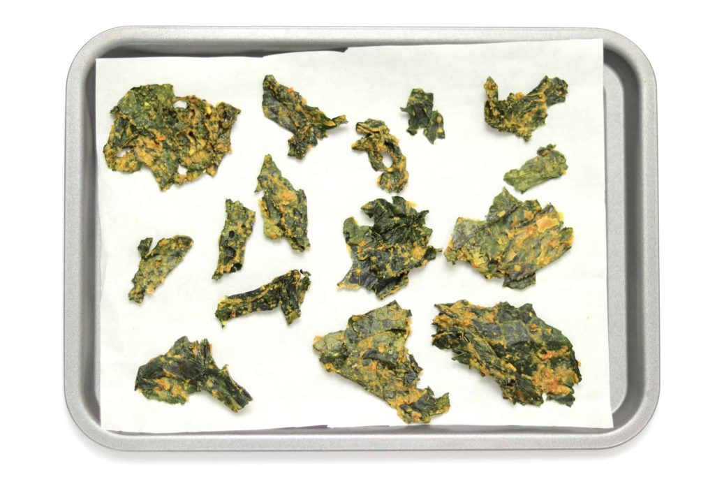 Kale chips spread out on a parchment paper lined baking tray
