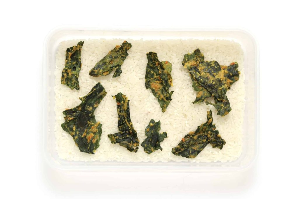 Crispy kale chips stored with rice in an airtight container to prevent moisture