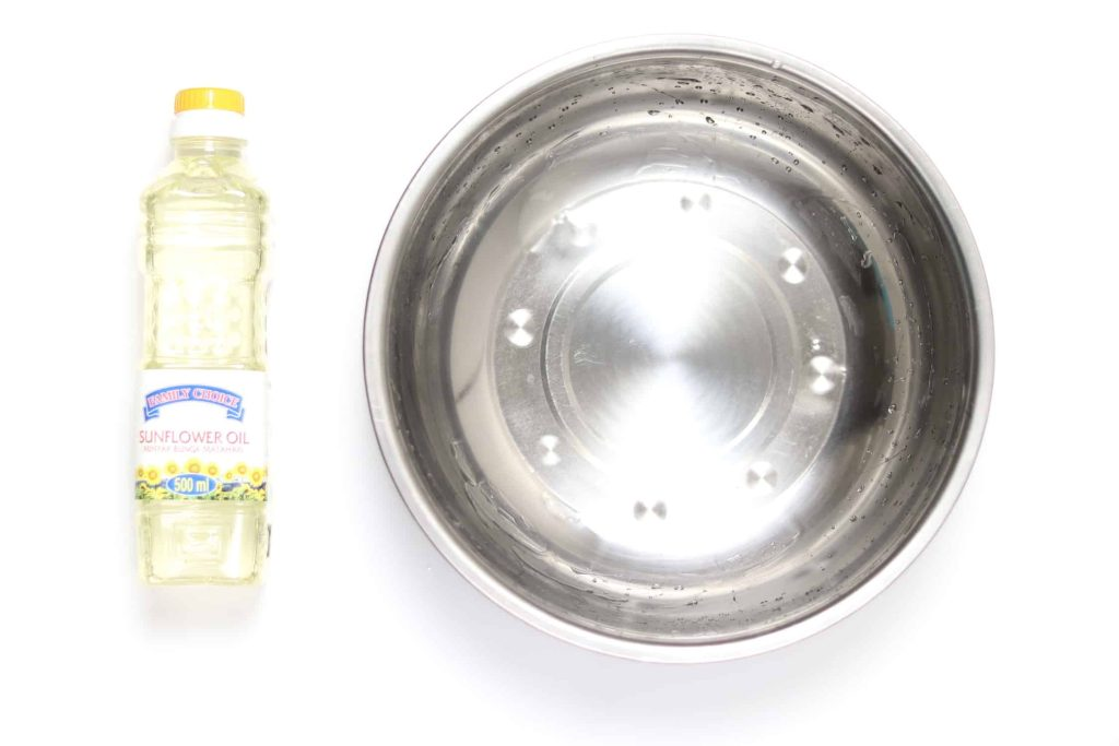 A bottle of sunflower oil next to a large metal bowl covered in oil without popcorn kernels.