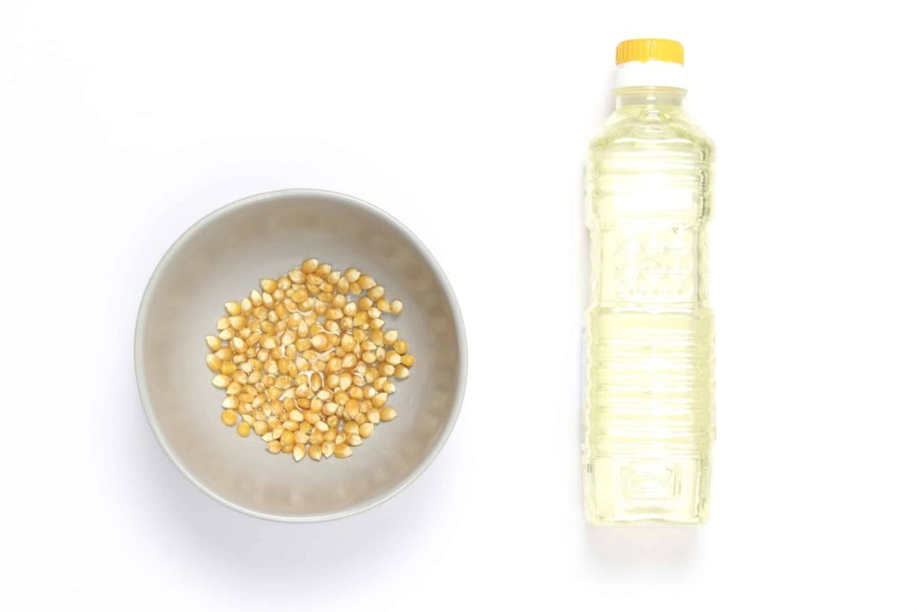 Popcorn kernels soaked in oil in a bowl before popping.
