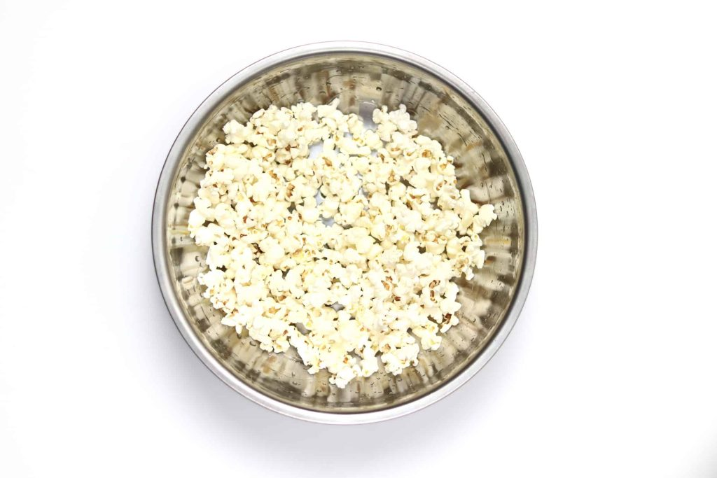 Freshly popped popcorn in a metal bowl with a light coating of oil and seasonings.