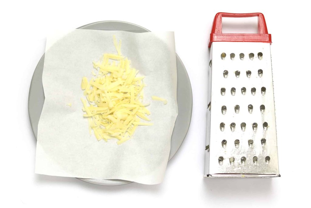 Shredded cheese sitting on top of wax paper.