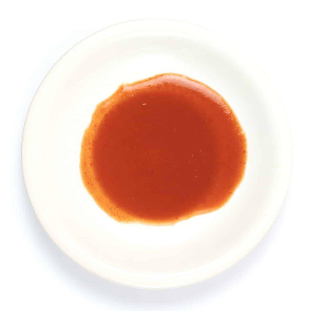 Thin, runny buffalo sauce on a small plate