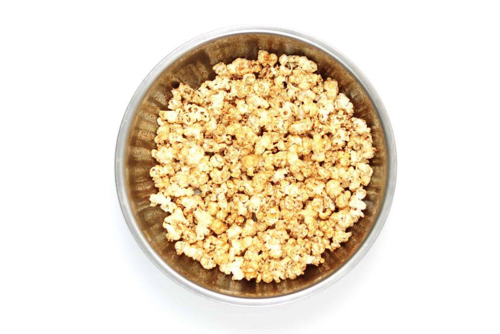 Popcorn coated in sweet paprika seasoning in a large metal bowl