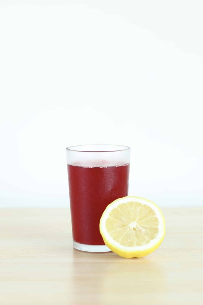 Cranberry juice and half a lemon side by side