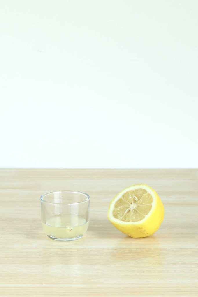 Fresh lemon juice in small glass jar next to freshly squeezed lemon