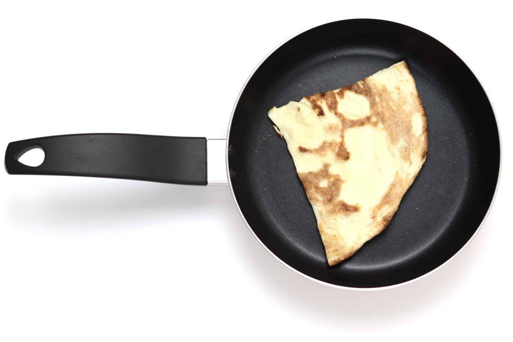 Naan face down in hot skillet