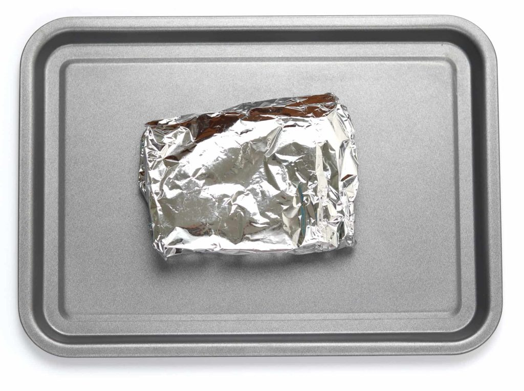 Piece of naan bread wrapped up in a foil parcel on a baking tray