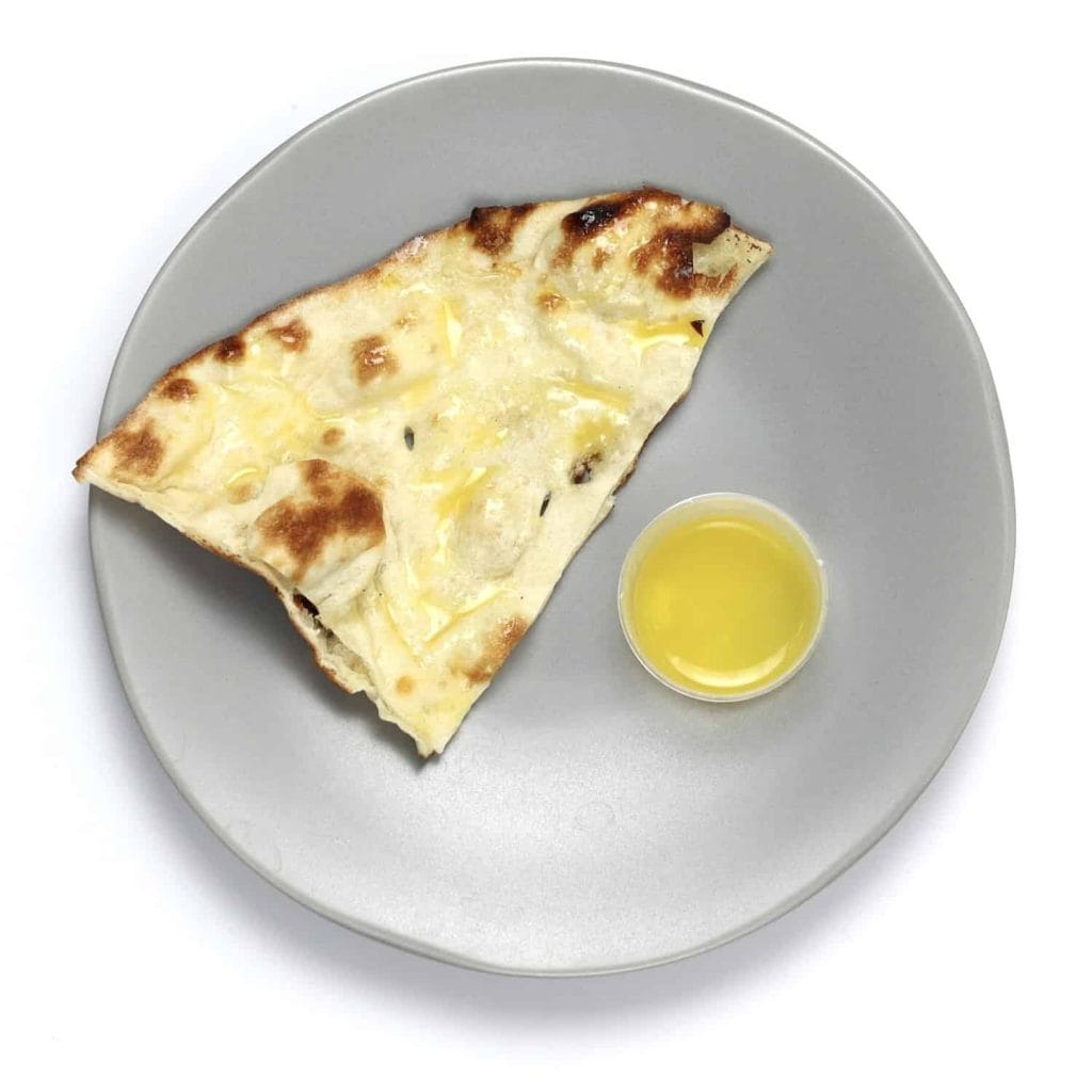 Piece of naan bread brushed in hot, melted ghee