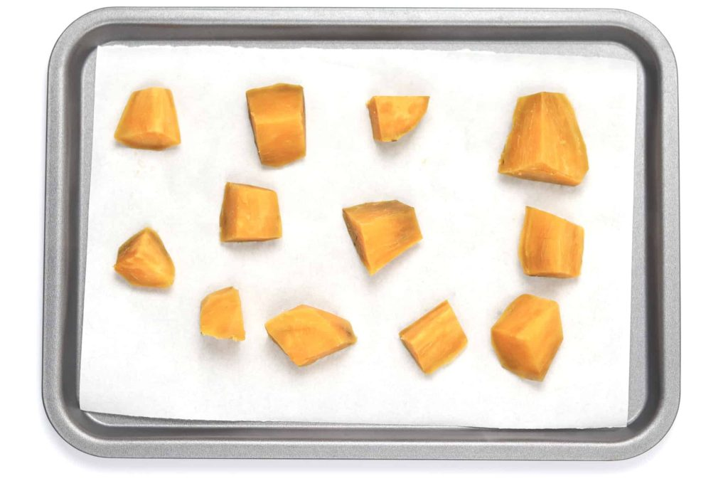 Cooked cut sweet potato on baking tray ready for flash freezing