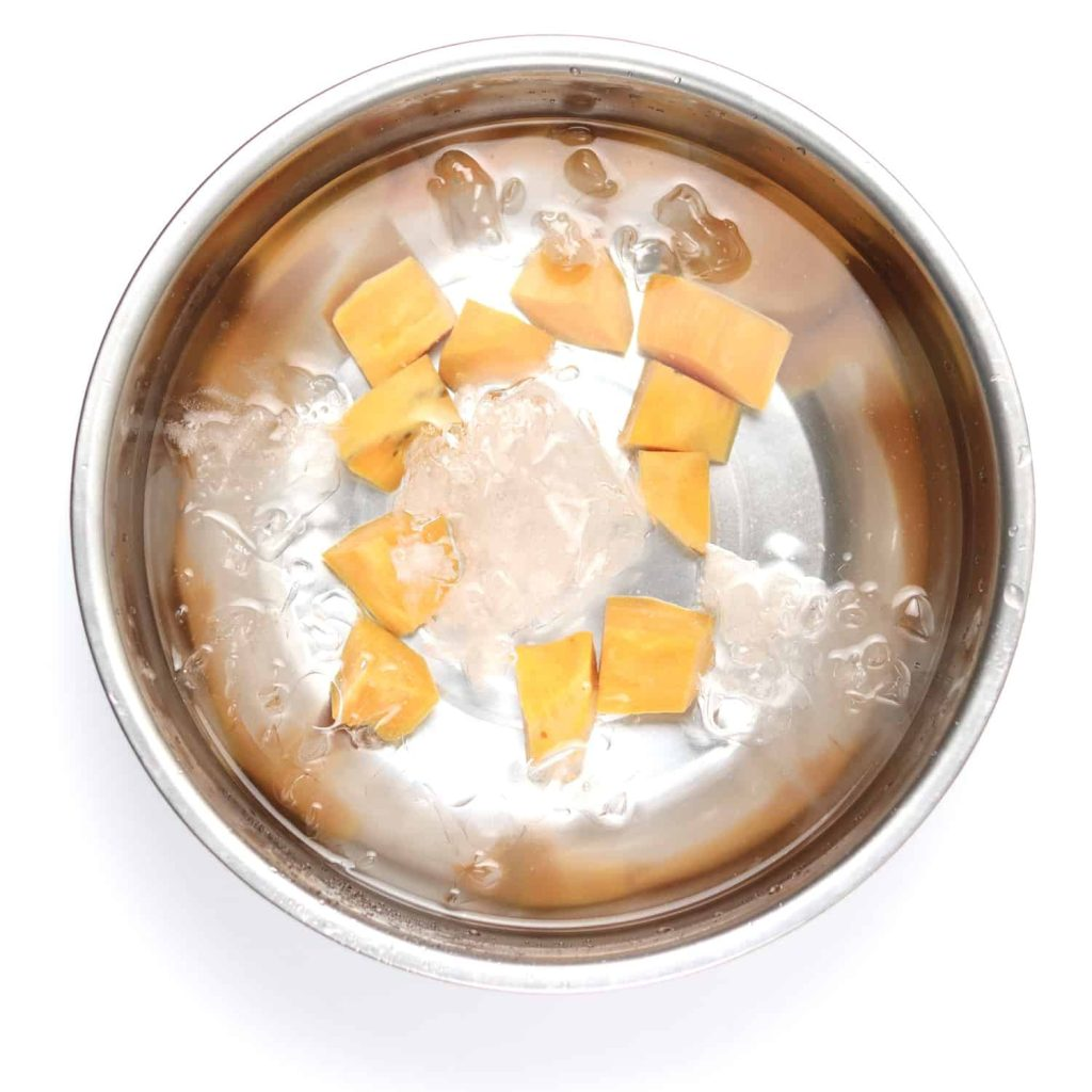 Cut sweet potatoes being blanched in ice water