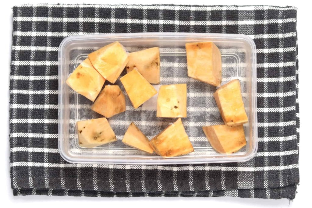 Cut sweet potato being submerged in cold water ready for refrigeration